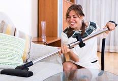 Ευτυχές ενήλικο σκουπίζοντας με ηλεκτρική σκούπα πάτωμα κοριτσιών Στοκ Φωτογραφία
