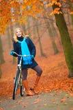 Ευτυχές ενεργό οδηγώντας ποδήλατο γυναικών στο πάρκο φθινοπώρου Στοκ Φωτογραφία