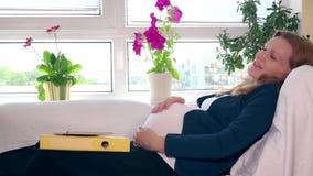 Ευτυχές εξαντλημένο έγκυο θηλυκό χάδι αυτή tummy στο κρεβάτι και το χαμόγελο απόθεμα βίντεο