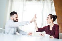 Ευτυχές επιτυχές businesspeople δύο που δίνει υψηλά πέντε στη συνεδρίαση Στοκ Εικόνες