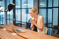 Ευτυχές επιχειρησιακό ξανθό κορίτσι που χρησιμοποιεί ένα lap-top σε ένα γραφείο Στοκ εικόνες με δικαίωμα ελεύθερης χρήσης