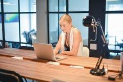 Ευτυχές επιχειρησιακό ξανθό κορίτσι που χρησιμοποιεί ένα lap-top σε ένα γραφείο Στοκ Εικόνες