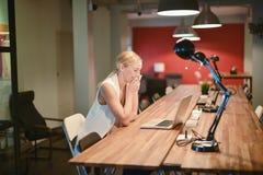 Ευτυχές επιχειρησιακό ξανθό κορίτσι που χρησιμοποιεί ένα lap-top σε ένα γραφείο Στοκ φωτογραφίες με δικαίωμα ελεύθερης χρήσης