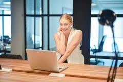 Ευτυχές επιχειρησιακό ξανθό κορίτσι που χρησιμοποιεί ένα lap-top σε ένα γραφείο Στοκ φωτογραφία με δικαίωμα ελεύθερης χρήσης