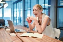 Ευτυχές επιχειρησιακό ξανθό κορίτσι που χρησιμοποιεί ένα lap-top σε ένα γραφείο Στοκ εικόνα με δικαίωμα ελεύθερης χρήσης
