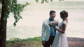 Ευτυχές ερωτευμένο μερίδιο ζευγών η ημέρα γάμου τους Στέκονται σε μια όχθη ποταμού, μιλούν και γελούν Όμορφες εξαρτήσεις, ανθοδέσ φιλμ μικρού μήκους
