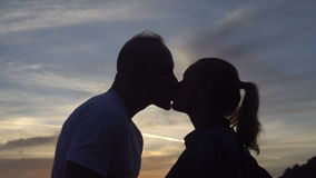 Ευτυχές ερωτευμένο φίλημα ζευγών στεμένος σε μια όμορφη ανατολή στεγών και προσοχής απόθεμα βίντεο