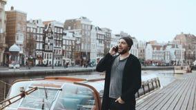 Ευτυχές ευρωπαϊκό περπάτημα ατόμων, που μιλά στο τηλέφωνο 4K Περιστασιακός δημιουργικός γενειοφόρος επιχειρηματίας Ανάχωμα ποταμώ φιλμ μικρού μήκους