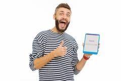 Ευτυχές ευχαριστημένο άτομο που απολαμβάνει χρησιμοποιώντας έναν ιστοχώρο αναζήτησης στοκ εικόνα
