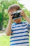 Ευτυχές εύθυμο αγόρι με μια κάμερα, το μωρό που φωτογραφίζεται υπαίθρια Στοκ Φωτογραφίες