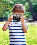 Ευτυχές εύθυμο αγόρι με μια κάμερα, το μωρό που φωτογραφίζεται υπαίθρια Στοκ φωτογραφία με δικαίωμα ελεύθερης χρήσης