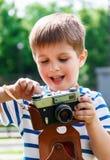 Ευτυχές εύθυμο αγόρι με μια κάμερα, το μωρό που φωτογραφίζεται υπαίθρια Στοκ Εικόνες