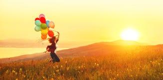 Ευτυχές εύθυμο κορίτσι με τα μπαλόνια που τρέχουν πέρα από το λιβάδι στο sunse Στοκ εικόνες με δικαίωμα ελεύθερης χρήσης