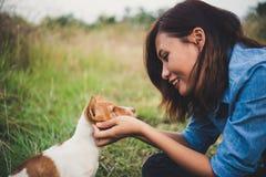 Ευτυχές εύθυμο παιχνίδι κοριτσιών hipster με το σκυλί της στο πάρκο dur Στοκ εικόνες με δικαίωμα ελεύθερης χρήσης