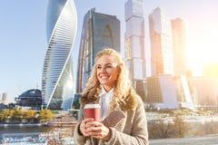 Ευτυχές ελκυστικό κορίτσι με τον καφέ που περπατά την ηλιόλουστη ημέρα φθινοπώρου Στοκ Εικόνες