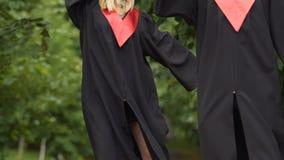 Ευτυχές ζευγάρι των απόφοιτων φοιτητών που χορεύουν και που γύρω, που κρατά τα διπλώματα φιλμ μικρού μήκους