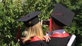 Ευτυχές ζευγάρι των πτυχιούχων που παίρνουν selfie στο smartphone στο πάρκο κοντά στην ακαδημία απόθεμα βίντεο