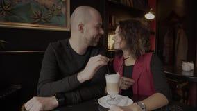 Ευτυχές ζευγάρι των newlyweds που κάθονται σε έναν καφέ και που πίνουν ένα latte από ένα φλυτζάνι απόθεμα βίντεο