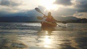 Ευτυχές ζευγών χαμόγελου κατά μήκος της θάλασσας στο όμορφο θερινό ηλιοβασίλεμα Τουρίστες που κωπηλατούν το καγιάκ, ομαδική εργασ απόθεμα βίντεο