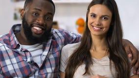 Ευτυχές ζεύγος αναμιγνύω-φυλών που περιμένει το μωρό και που χαμογελά, κλινική οικογενειακού προγραμματισμού απόθεμα βίντεο