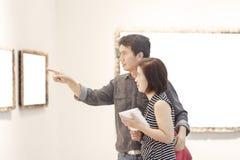 Ευτυχές ζεύγος Ασιάτης που εξετάζει το γκαλερί τέχνης στοκ φωτογραφία με δικαίωμα ελεύθερης χρήσης