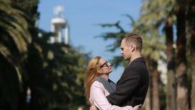 Ευτυχές ζεύγος ερωτευμένο έχοντας τη διασκέδαση Χαριτωμένη όμορφη γυναίκα με έναν όμορφο άνδρα σε ένα φίλημα παλτών Ενάντια στο σ απόθεμα βίντεο