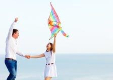 Ευτυχές ζεύγος ερωτευμένο με το πέταγμα ενός ικτίνου στην παραλία Στοκ Φωτογραφία