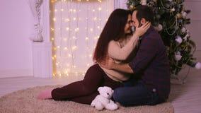 Ευτυχές ζεύγος ερωτευμένο στη συνεδρίαση Χριστουγέννων πριν από την εστία Απολαύστε τις ευτυχείς στιγμές της ζωής του απόθεμα βίντεο