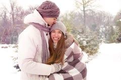 Ευτυχές ζεύγος ερωτευμένο στο πάρκο το χειμώνα με τις ελαφριές διαρροές Στοκ Φωτογραφίες