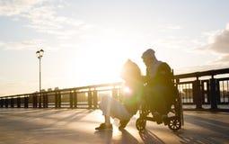 Ευτυχές ζεύγος - η νέα γυναίκα με το με ειδικές ανάγκες άνδρα στην αναπηρική καρέκλα στηρίζεται μαζί υπαίθρια Στοκ Φωτογραφία
