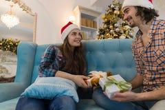 Ευτυχές ζεύγος διακοπών Χριστουγέννων που δίνει στην παρούσα ένδυση κιβωτίων το νέο χαμόγελο καπέλων ΚΑΠ, ανδρών και γυναικών San Στοκ Εικόνα