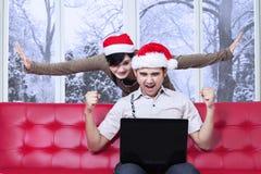 Ευτυχές ζεύγος μετά από την αμοιβή on-line στη ημέρα των Χριστουγέννων στοκ εικόνες