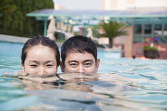 Ευτυχές ζεύγος με μισό υποβρύχιο προσώπου στη λίμνη που εξετάζει τη κάμερα στοκ εικόνα με δικαίωμα ελεύθερης χρήσης