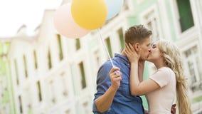 Ευτυχές ζεύγος με τα ζωηρόχρωμα μπαλόνια αέρα που φιλά στην οδό, τρυφερή σχέση στοκ εικόνα
