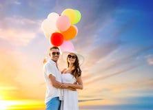 Ευτυχές ζεύγος με τα μπαλόνια πέρα από τον ουρανό ηλιοβασιλέματος Στοκ φωτογραφίες με δικαίωμα ελεύθερης χρήσης