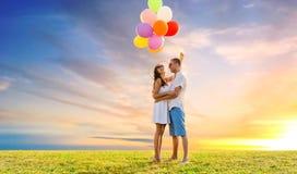 Ευτυχές ζεύγος με τα μπαλόνια πέρα από τον ουρανό ηλιοβασιλέματος Στοκ εικόνες με δικαίωμα ελεύθερης χρήσης