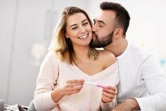 Ευτυχές ζεύγος με τη δοκιμή εγκυμοσύνης στην κρεβατοκάμαρα στοκ εικόνες