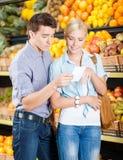 Ευτυχές ζεύγος με τον κατάλογο αγορών ενάντια στους σωρούς των φρούτων στοκ εικόνα με δικαίωμα ελεύθερης χρήσης