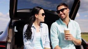 Ευτυχές ζεύγος με τον καφέ στον κορμό 11 αυτοκινήτων hatchback απόθεμα βίντεο