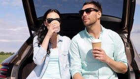 Ευτυχές ζεύγος με τον καφέ στον κορμό 10 αυτοκινήτων hatchback φιλμ μικρού μήκους