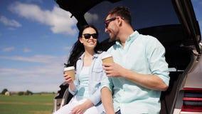 Ευτυχές ζεύγος με τον καφέ στον κορμό 39 αυτοκινήτων hatchback απόθεμα βίντεο