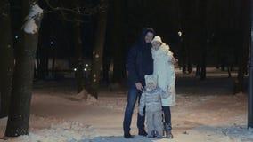 Ευτυχές ζεύγος με το αγκάλιασμα κορών στο χειμερινό πάρκο βραδιού απόθεμα βίντεο