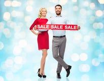 Ευτυχές ζεύγος με το κόκκινο σημάδι πώλησης πέρα από τα μπλε φω'τα Στοκ φωτογραφία με δικαίωμα ελεύθερης χρήσης
