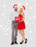 Ευτυχές ζεύγος με το κόκκινο σημάδι πώλησης πέρα από το χιόνι Στοκ εικόνες με δικαίωμα ελεύθερης χρήσης