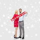 Ευτυχές ζεύγος με το κόκκινο σημάδι πώλησης πέρα από το χιόνι Στοκ Φωτογραφία