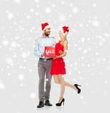 Ευτυχές ζεύγος με το κόκκινο σημάδι πώλησης πέρα από το χιόνι Στοκ φωτογραφίες με δικαίωμα ελεύθερης χρήσης