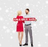 Ευτυχές ζεύγος με το κόκκινο σημάδι πώλησης πέρα από το χιόνι Στοκ φωτογραφία με δικαίωμα ελεύθερης χρήσης