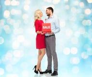 Ευτυχές ζεύγος με το κόκκινο σημάδι πώλησης Στοκ φωτογραφία με δικαίωμα ελεύθερης χρήσης