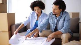 Ευτυχές ζεύγος με το σχεδιάγραμμα και κιβώτια στο νέο σπίτι απόθεμα βίντεο