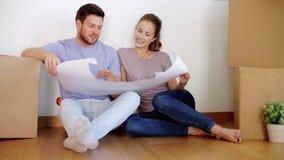 Ευτυχές ζεύγος με το σχεδιάγραμμα στο νέο σπίτι απόθεμα βίντεο